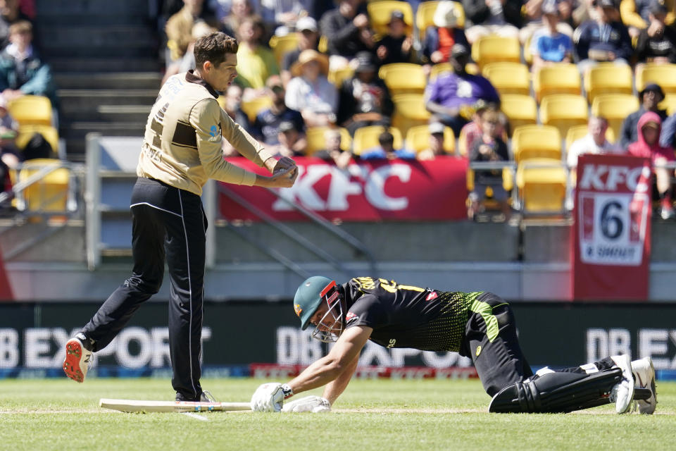 Australia's Marcus Stoinis, right, reaches to make his ground as New Zealand's Mitchell Santner takes the ball during their 5th T20 cricket international match at Wellington Regional Stadium in Wellington, New Zealand, Sunday, March 7 , 2021. (John Cowpland/Photosport via AP)