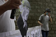Pro-China supporters displays a picture of U.S. President Donald Trump during a protest against the U.S. sanctions outside the U.S. Consulate in Hong Kong Saturday, Aug. 8, 2020. The U.S. on Friday imposed sanctions on Hong Kong officials, including the pro-China leader of the government, accusing them of cooperating with Beijing's effort to undermine autonomy and crack down on freedom in the former British colony. (AP Photo/Vincent Yu)