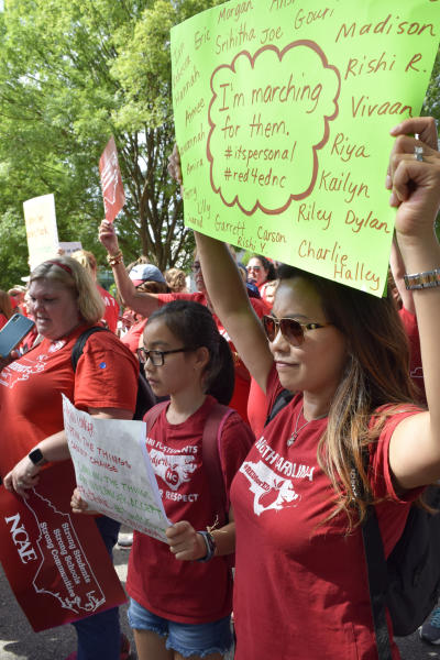 Fifth grade elementary school teacher Shirley Pyon, 41, marches in Raleigh, N.C., as part of a teacher's rally in the state capitol, Wednesday, May 1, 2019. She holds a sign with the names of all 28 students in her fifth grade class at Mills Park Elementary School in Cary, N.C., because she said this march is for students. (AP Photo/Amanda Morris)