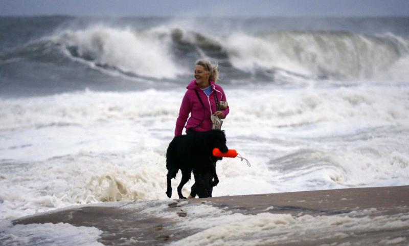 Annemarie Jarman and her dog Bruges walk along the edge of the beach that is mostly empty as Hurricane Sandy bears down on the East Coast, Saturday, Oct. 27, 2012, in Ocean City, Md. Hurricane Sandy, upgraded again Saturday just hours after forecasters said it had weakened to a tropical storm, was barreling north from the Caribbean and was expected to make landfall early Tuesday near the Delaware coast, then hit two winter weather systems as it moves inland, creating a hybrid monster storm. (AP Photo/Alex Brandon)