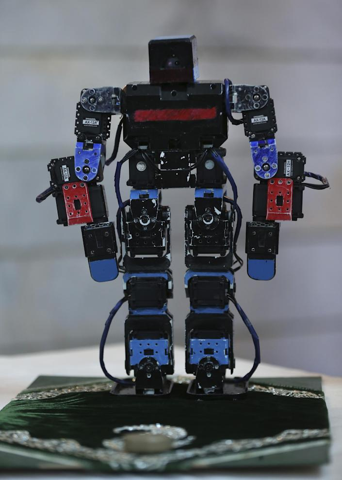 """In this picture taken on Saturday, Feb. 22, 2014, Veldan, a humanoid praying robot which is built by Iranian school teacher Akbar Rezaie, is seen at his home in the city of Varamin some 21 miles (35 kilometers) south of the capital Tehran, Iran. Rezaei who has built a robot to show to children how to execute daily prayers, has innovated an amusing way of encouraging young children to say their daily prayers by using the science of robotics. Out of personal interest and unrelated to his field of study, Akbar Rezaei attended private robotics classes and acquired the skill of assembling and developing customized humanoid robots. He built the robot at home with basic tools and gave it the designation """"Veldan"""", a term mentioned in Quran meaning: """"Youth of Heaven"""". By applying some mechanical modifications such as adding up two extra engines Akbar Rezaei managed to let the robot perform praying movements, such as prostration, more easily. (AP Photo/Vahid Salemi)"""