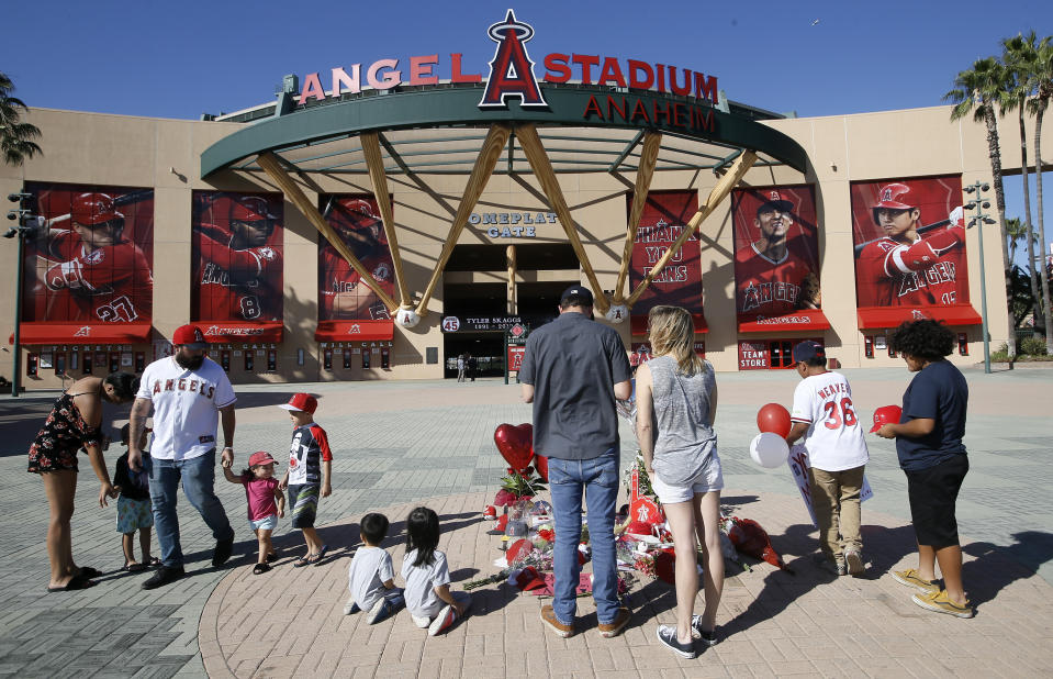 Mourners stand at a memorial to give their condolences for Los Angeles Angels pitcher Tyler Skaggs at Angel Stadium in Anaheim, Calif., Monday, July 1, 2019. Skaggs died at the age of 27, stunning Major League Baseball and leading to the postponement of the team's game against the Texas Rangers on Monday. (AP Photo/Alex Gallardo)