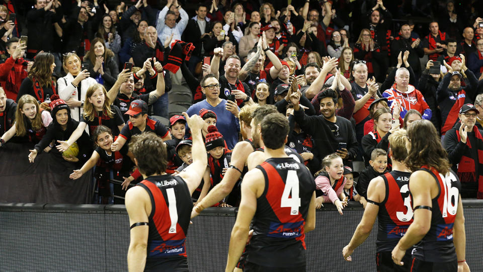 Essendon players, pictured here acknowledging their fans after the round 10 match against North Melbourne at Marvel Stadium.
