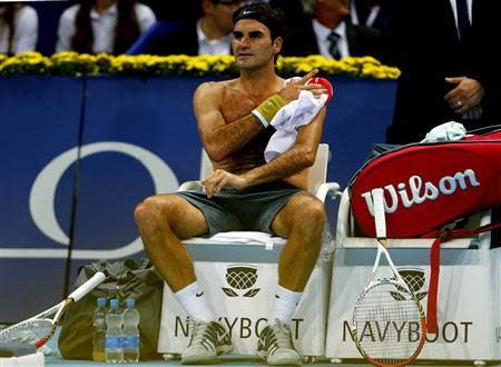 Switzerland's Roger Federer changes his jersey during his match against Adrian Mannarino of France at the Swiss Indoors ATP tennis tournament in Basel October 21, 2013. REUTERS/Arnd Wiegmann