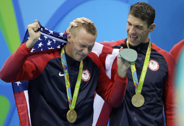 FILE - In this Aug. 8, 2016, file photo, Caeleb Dressel, left, cries with Michael Phelps after the medal ceremony for the men's 4x100-meter freestyle relay during the swimming competitions at the 2016 Summer Olympics, in Rio de Janeiro, Brazil. At two years to the day the Tokyo Olympics open, Katie Ledecky is swimming as fast as ever, Caeleb Dressel is being heralded as a potential Phelps, and Missy Franklin is attempting a comeback. And Ryan Lochte is newly banned again.(AP Photo/David J. Phillip, File)