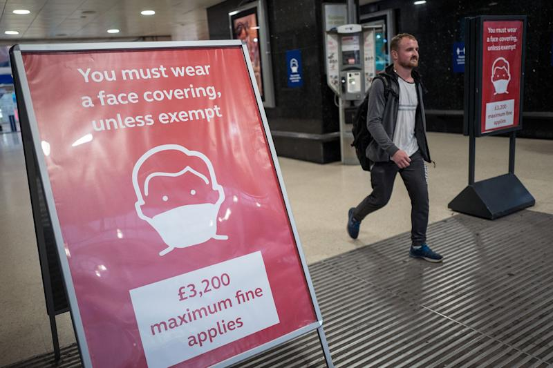 A man, not wearing a face covering, passes signs telling travellers they must wear face mask unless they are exempt, as he leaves Victoria station during the evening 'rush hour' in central London on September 23, 2020. - The UK on Wednesday reported 6,178 new coronavirus cases, a marked jump in the daily infection rate that comes a day after Prime Minister Boris Johnson unveiled new nationwide restrictions. (Photo by Tolga AKMEN / AFP) (Photo by TOLGA AKMEN/AFP via Getty Images)