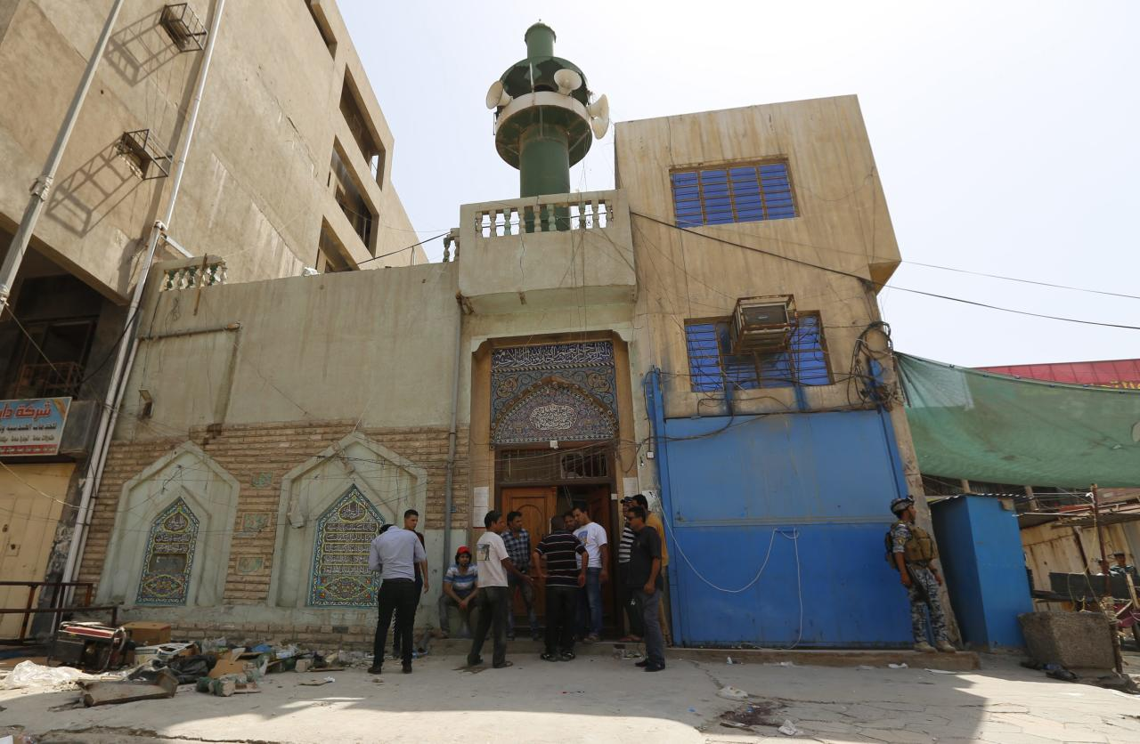 People gather at the site of a suicide bomber on a Shi'ite mosque in Baghdad May 27, 2014. The attack by a suicide bomber on a Shi'ite mosque in Baghdad killed 19 people and wounded 36, police sources said. REUTERS/Thaier Al-Sudani (IRAQ - Tags: CIVIL UNREST POLITICS CRIME LAW)