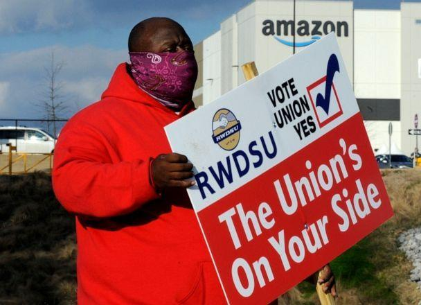 Michael Foster of the Retail, Wholesale and Department Store Union holds a sign on Feb. 9, 2021, outside an Amazon facility where labor is trying to organize workers in Bessemer, Alabama. (Jay Reeves/AP)