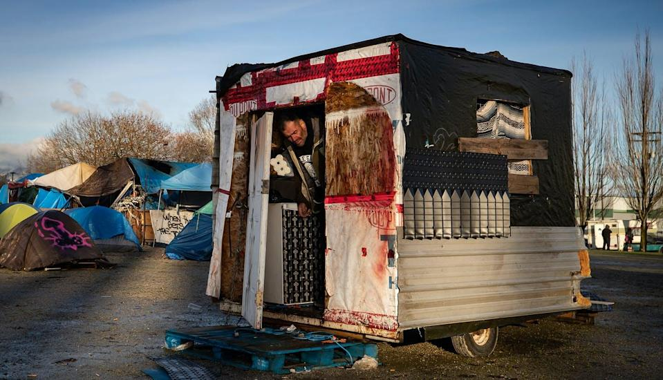 "<span class=""caption"">A man steps out of the trailer he lives in at a homeless encampment at Strathcona Park in Vancouver in December 2020. </span> <span class=""attribution""><span class=""source"">THE CANADIAN PRESS/Darryl Dyck</span></span>"