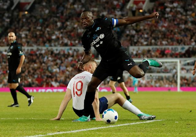 Soccer Football - Soccer Aid 2018 - England v Soccer Aid World XI - Old Trafford, Manchester, Britain - June 10, 2018 World XI's Usain Bolt in action with England's Freddie Flintoff Action Images via Reuters/Andrew Boyers