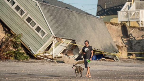 PHOTO: A man walks his dog by a beachfront home destroyed by Hurricane Irma in Vilano Beach, Fla, Sept. 13, 2017. (Sean Rayford/Getty Images, FILE)