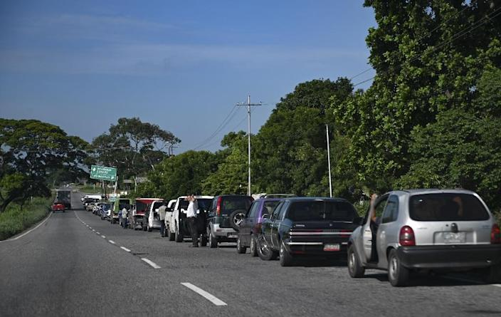 Drivers queue at a gas station along a highway in Venezuela. A dollar can technically buy almost 600 million liters of fuel (AFP Photo/Yuri CORTEZ)