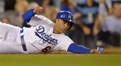 Los Angeles Dodgers' Jerry Hairston Jr. reaches out for the plate as he scores on a single by Mark Ellis during the fourth inning of the Dodgers' baseball game against the Colorado Rockies, Thursday, July 11, 2013, in Los Angeles. (AP Photo/Mark J. Terrill)