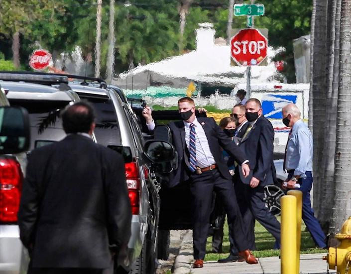 Joe Biden, right, is ushered by his Secret Service detail as he leaves the Little Haiti Cultural Complex during a brief visit to Little Haiti on Monday, October 5, 2020.