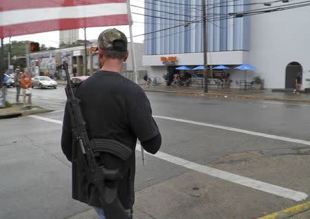 A pro-gun advocate walks down the street outside the University of Texas ahead of a 'mock mass shooting' event where they used cardboard cut-outs rifles, the simulated bangs of bullets on bullhorns and doused fake victims with fake blood, in Austin, Texas, December 12, 2015.   REUTERS/Jon Herskovitz
