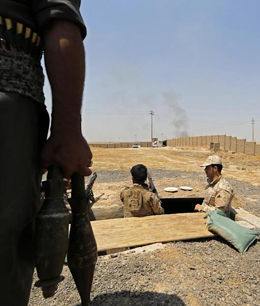Iraqi Kurdish forces take position as they fight jihadist militants from the Islamic State of Iraq and the Levant (ISIL) in the northern village of Bashir, on June 29, 2014 (AFP Photo/Karim Sahib)