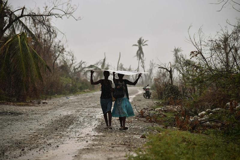 Women walk protecting themself from the rain, in the commune of Chadonyer, in Les Cayes, in the southwest of Haiti (AFP Photo/Hector Retamal)