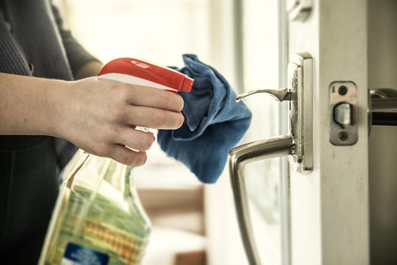 Close-up of woman disinfecting door handle with spray bottle