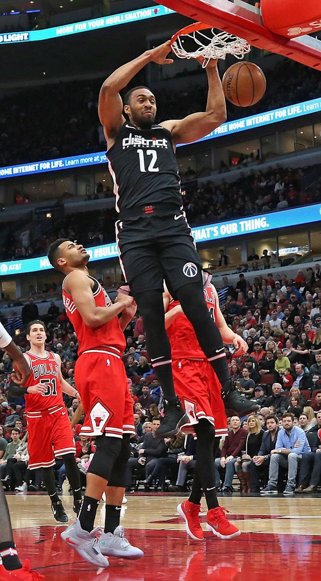 CHICAGO, ILLINOIS - FEBRUARY 09: Jabari Parker #12 of the Washington Wizards dunks over Timothe Luwawu-Cabarrot #7 and Lauri Markkanen #24 of the Chicago Bulls at the United Center on February 09, 2019 in Chicago, Illinois. (Photo by Jonathan Daniel/Getty Images)