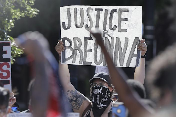 """A protester holds a sign during a protest in Louisville, Ky., over the deaths of George Floyd and Breonna Taylor. <span class=""""copyright"""">(Associated Press)</span>"""