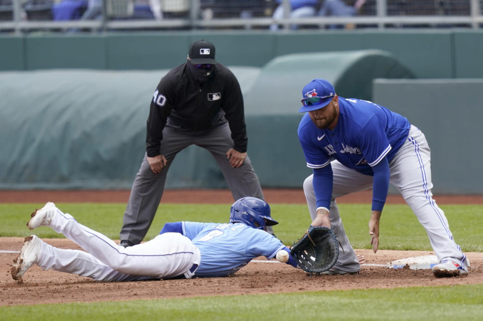Kansas City Royals Nicky Lopez, left, dives back safely ahead of the tag by Toronto Blue Jays first baseman Rowdy Tellez, right, during the second inning of a baseball game at Kauffman Stadium in Kansas City, Mo., Sunday, April 18, 2021. (AP Photo/Orlin Wagner)