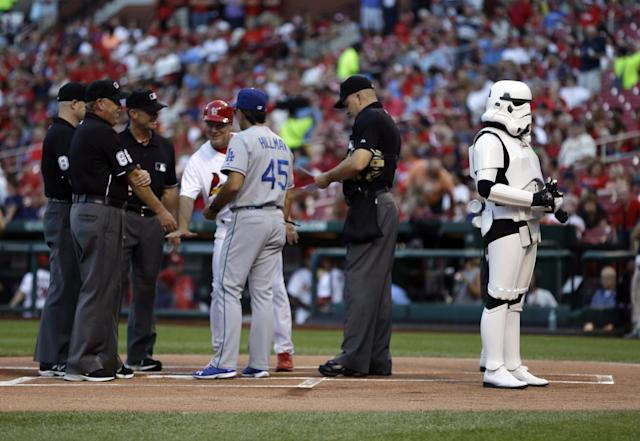 """An imperial storm trooper, right, stands guard as the line-up cards are exchanged on """"Star Wars"""" night at Busch Stadium before a baseball game between the St. Louis Cardinals and the Los Angeles Dodgers on Wednesday, Aug. 7, 2013, in St. Louis. (AP Photo/Jeff Roberson)"""