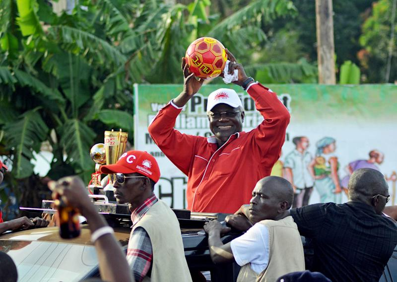 In this Sunday, Nov. 11, 2012 photo, President Ernest Bai Koroma throws soccer balls to his supporters during the party's final rally ahead of presidential elections, in Freetown, Sierra Leone. Red soccer balls have become a symbol of the president's campaign. Ten years after the end of a devastating civil war, Sierra Leone will go to the polls on Saturday in an election that hinges on which candidate can best uplift this West African country trying to shed its past and benefit from its diamond riches.(AP Photo/Tommy Trenchard)