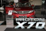 A man enters a Proton X70 car at its headquarters in Subang Jaya
