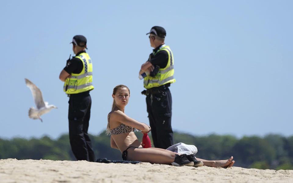 A woman sunbathes, while police patrol nearby, as a meeting of G7 leaders takes place in St. Ives, Cornwall, England, Saturday, June 12, 2021. Leaders of the G7 gather for a second day of meetings on Saturday, in which they will discuss COVID-19, climate, foreign policy and the economy. (AP Photo/Jon Super)
