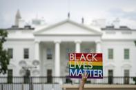 A protester holds up a 'Black Lives Matter' sign outside the White House