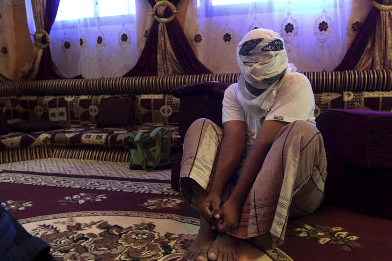 FILE - In this May 11, 2017 file photo, a former detainee covers his face for fear of being detained again, as he shows how he was kept in handcuffs and leg shackles while held in a secret prison at Riyan airport in the Yemeni city of Mukalla, in Aden, Yemen. On Tuesday, June 30, 2020, the Yemeni rights group, Mwatana Organization for Human Rights, accused both sides in the country's civil war of arbitrary detentions, forced disappearances and torture of hundreds of people in the past four years in unofficial detention centers across war-torn Yemen. The organization says it documented over 1,600 cases of arbitrary detentions, 770 cases of forced disappearances, 344 cases of torture and at least 66 deaths in secret prisons run by the warring sides since April 2016. (AP Photo/Maad El Zikry, File)