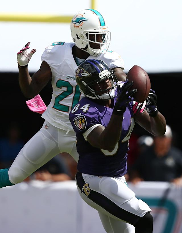 Baltimore Ravens tight end Ed Dickson (84) catches a pass over Miami Dolphins free safety Reshad Jones (20) during the first half of an NFL football game, Sunday, Oct. 6, 2013, in Miami Gardens, Fla. (AP Photo/J Pat Carter)