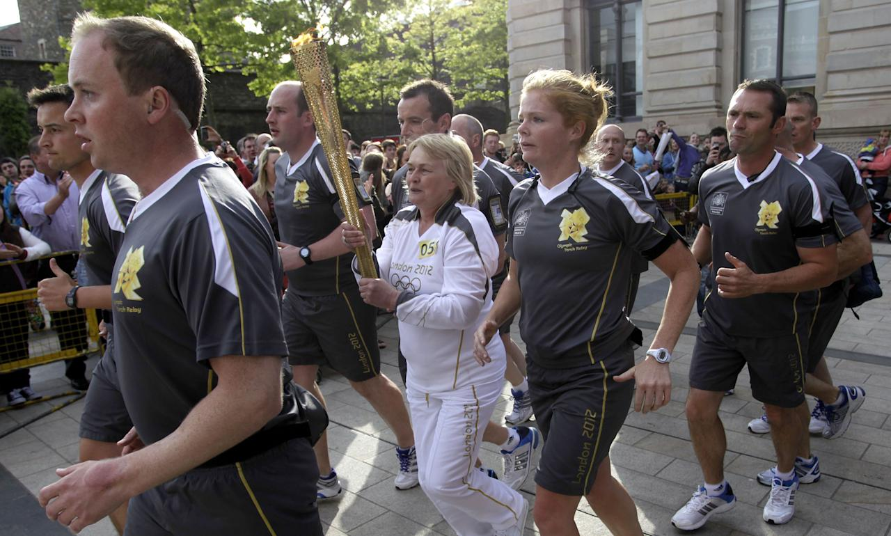 The Olypic torch is rerouted away from protesters in Guildhall Street, Londonderry, Northern Ireland, Monday, June 4, 2012. Dissident Republican protesters caused the Olympic torch to be rerouted Monday. (AP Photo/Peter Morrison)