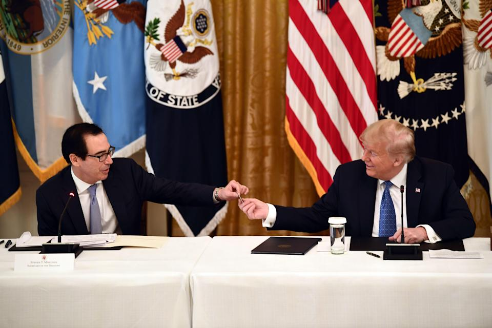 US Treasury Secretary Steve Mnuchin shows US President Donald Trump a pre-paid debit card during a meeting with his cabinet on May 19, 2020 in the Cabinet Room of the White House in Washington, DC. (Photo by BRENDAN SMIALOWSKI/AFP via Getty Images)