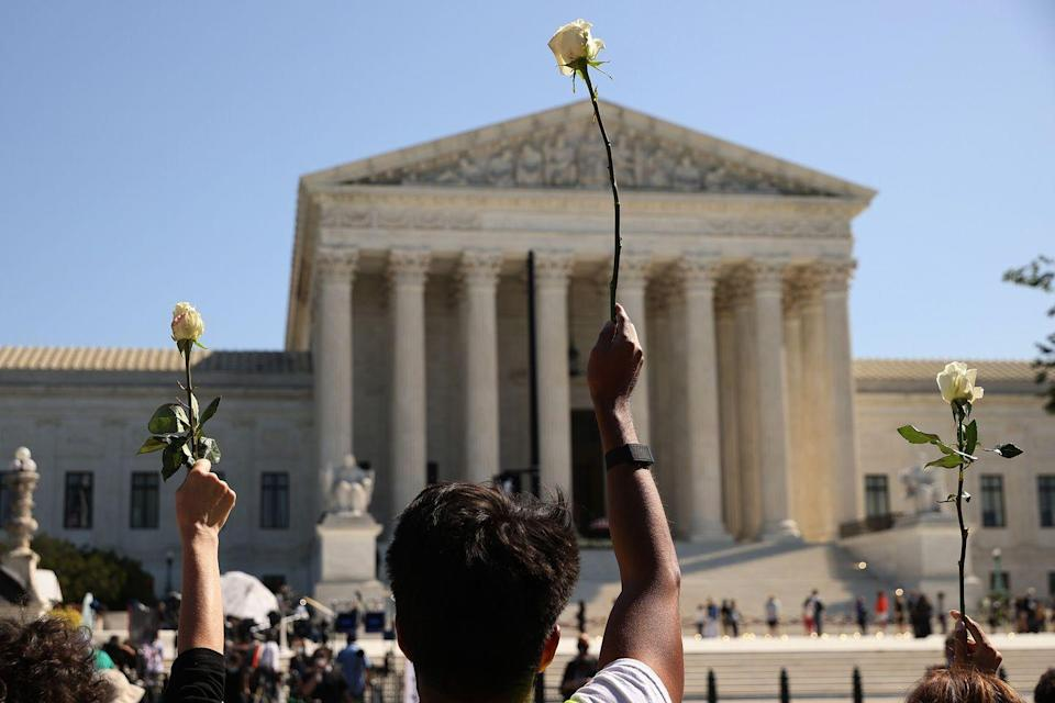 <p>Members of CASA, an advocacy organization for Latino and immigrant people, hold up white roses in honor of Associate Justice Ruth Bader Ginsburg as her flag-draped casket rests on the Lincoln catafalque on the west front of the U.S. Supreme Court September 23, 2020 in Washington, DC.</p>