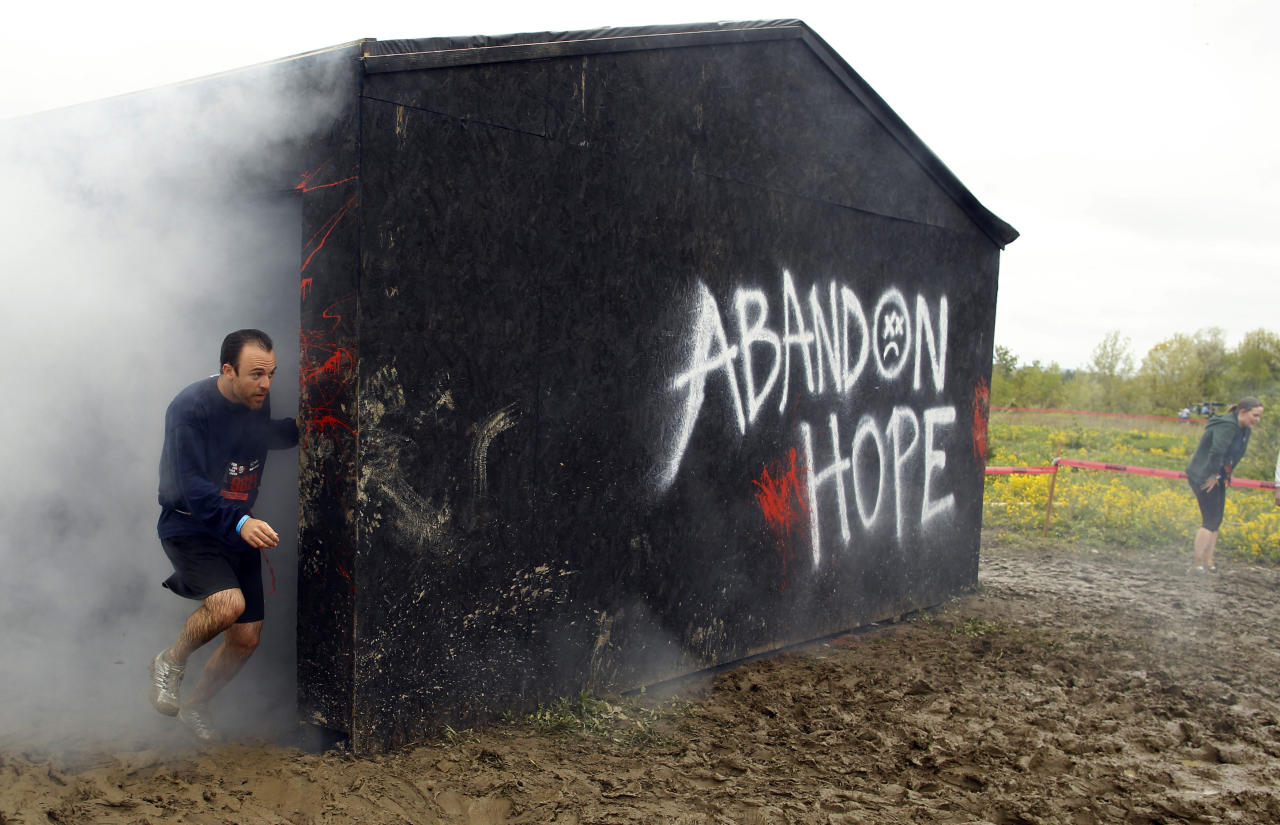 "Runners emerge from the smoke house on the ""Run for Your Lives"" 5K obstacle course race in Amesbury, Massachusetts May 5, 2012. Runners face man-made and natural obstacles on the course, while being chased by zombies, who try to take ""health"" flags off the runners belts.   REUTERS/Brian Snyder"
