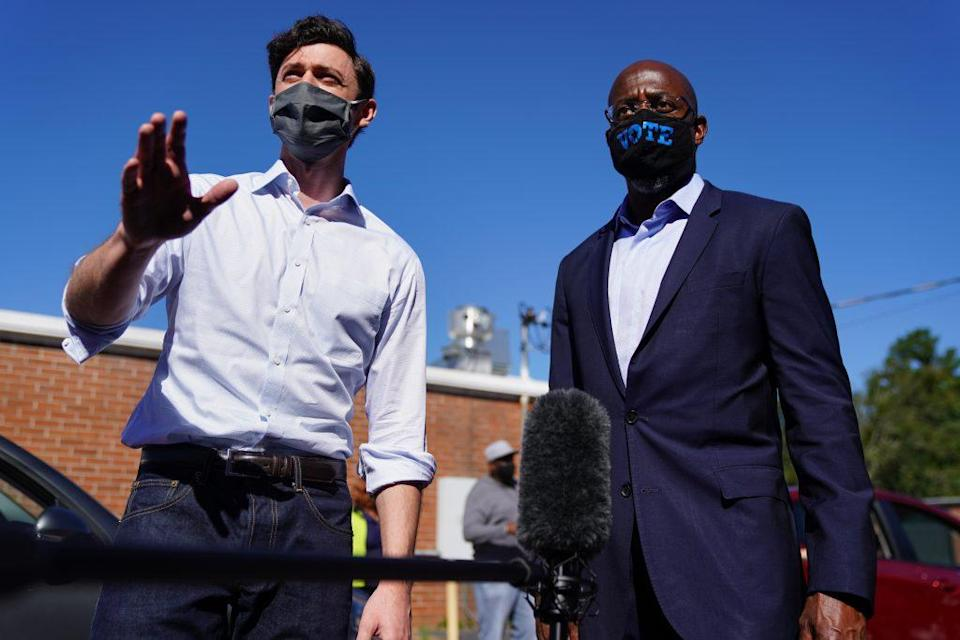 Democratic U.S. Senate candidates Jon Ossoff and Rev. Raphael Warnock hand out lawn signs at a campaign event on October 3, 2020 in Lithonia, Georgia. (Photo by Elijah Nouvelage/Getty Images)