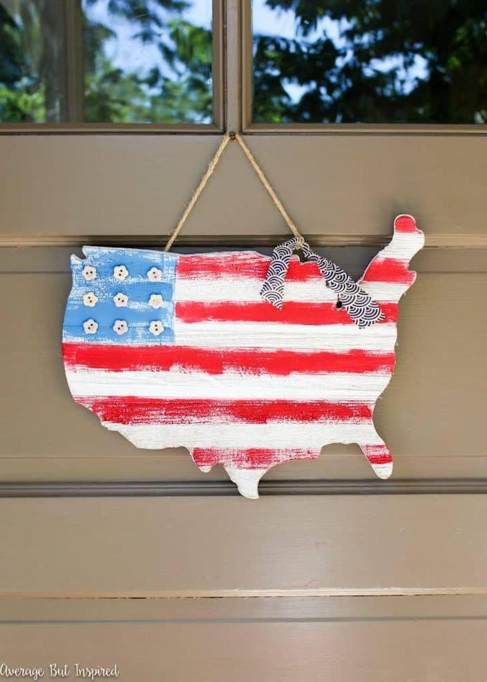 """<p>With the help of some paint, buttons, and fabric, you can turn an inexpensive wooden cutout into a unique Independence Day decoration.</p><p><strong><em>Get the tutorial from <a href=""""https://averageinspired.com/2016/06/usa-wooden-flag-map-door-hanger.html"""" rel=""""nofollow noopener"""" target=""""_blank"""" data-ylk=""""slk:Average But Inspired"""" class=""""link rapid-noclick-resp"""">Average But Inspired</a>. </em></strong></p>"""