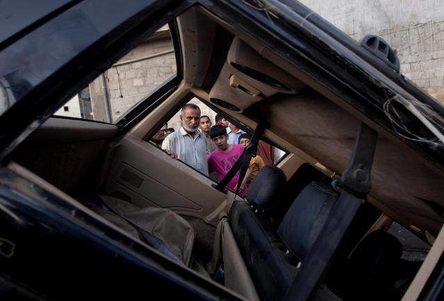 <p>Pakistani residents investigate damages of a vehicle caused by a bomb explosion early morning in Karachi, Pakistan, Aug. 7, 2013. A bomb blast that appeared to be targeting a provincial government minister killed many people before dawn Wednesday at a soccer field in southern Pakistan, the latest in a series of attacks that left tens dead across the country, officials said. (AP Photo/Shakil Adil) </p>