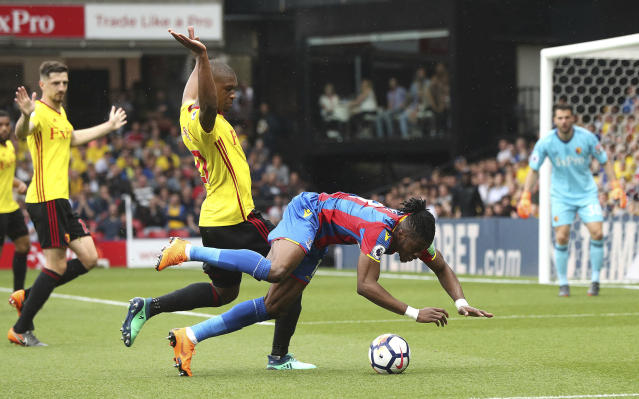 Watford's Christian Kabasele, left, and Crystal Palace's Wilfried Zaha battle for the ball during the English Premier League soccer match at Vicarage Road, Watford, England, Saturday April 21, 2018. (Jonathan Brady/PA via AP)