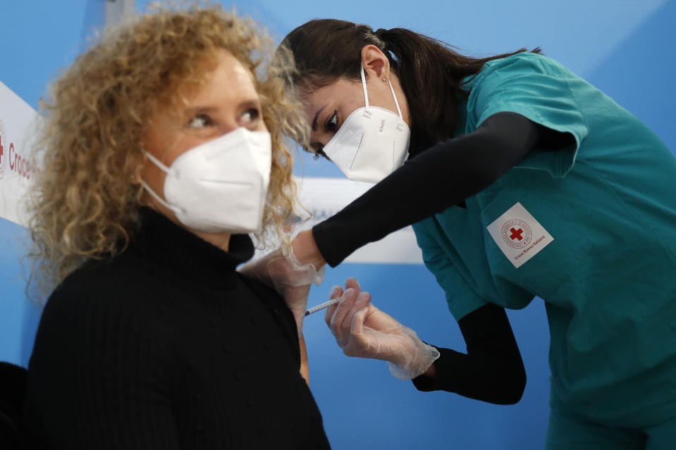 FILE - In this Feb. 11, 2021 file photo a health worker administers a dose of the AstraZeneca vaccine to a woman at a vaccination center set up in Fiumicino, near Rome's international airport. As Poland began vaccinating teachers on Friday Feb. 12, 2021 many say they are unhappy that they are getting AstraZeneca vaccines against the coronavirus, rather than the Pfizer shots earmarked for health care workers and the elderly. Nearly a year into the pandemic, many Europeans and others globally are desperate to get vaccinated and return to normal life. But many don't want just any vaccine. (AP Photo/Alessandra Tarantino, File)