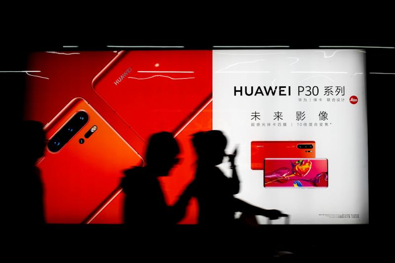 Commuters walk by the new Huawei P30 smartphone advertisement on display inside a subway station in Beijing Monday, May 13, 2019. China's intensified tariff war with the Trump administration is threatening Beijing's ambition to transform itself into the dominant player in global technology. (AP Photo/Andy Wong)