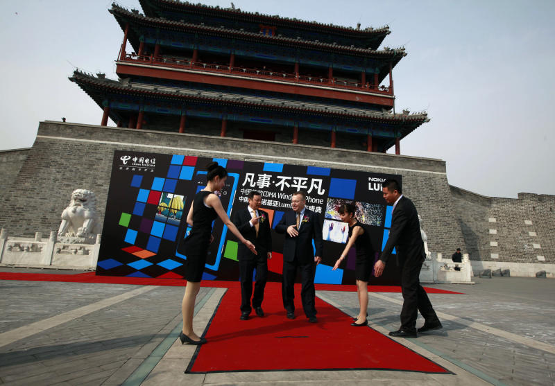 Nokia CEO Stephen Elop, third from right and Wang Xiaochu, Chairman of China Telecoms, second from left, are shown the way for a photo shoot as they arrive to attend the launch of the new Nokia smartphone Lumia 800C in Beijing, China, Wednesday, March 28, 2012. Struggling cellphone maker Nokia launched its first smartphone design for China on Wednesday, looking to the world's biggest mobile market to help drive a turnaround.(AP Photo/Ng Han Guan)