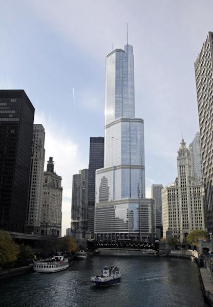 Boats move along the Chicago River near the Trump International Hotel and Tower, center, Friday, Nov. 8, 2013, in Chicago. The tower would have topped Willis Tower under one version of the designs. But Donald Trump said initial plans for a taller spire on top looked awkward. And some of those who purchased condominiums in the tower before its completion expressed concern about living in a taller building. (AP Photo/Kiichiro Sato)