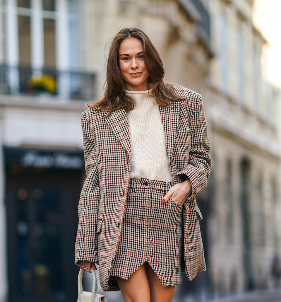 PARIS, FRANCE - NOVEMBER 28: Therese Hellström wears a full Zadig & Voltaire look made of a white wool pullover, a checked houndstooth pattern oversized blazer jacket with long sleeves, a short slit skirt, a white Jacquemus bag made of fabric, burgundy leather knee high pointy boots with high heels from Custommade, on November 28, 2020 in Paris, France. (Photo by Edward Berthelot/Getty Images)
