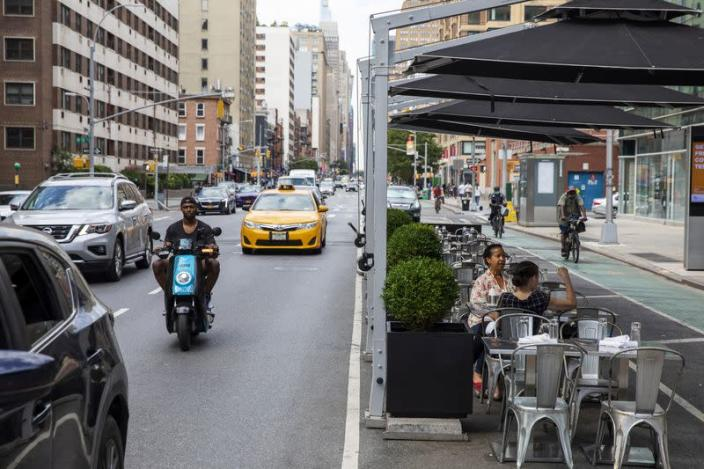 Customers sit in outdoor seating that is placed in parking spaces to follow health protocols for restaurants to slow the spread of Coronavirus (COVID-19) outside of a restaurant in New York City, New York