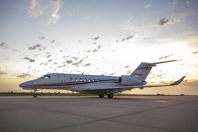 A Citation Longitude business jet parked in front of a sunset.