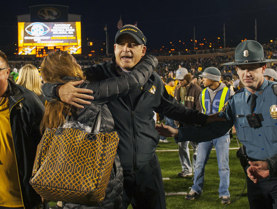 Missouri head coach Gary Pinkel, center, is hugged by fans after they defeated Arkansas 21-14 in an NCAA college football game Friday, Nov. 28, 2014, in Columbia, Mo. (AP Photo/L.G. Patterson)