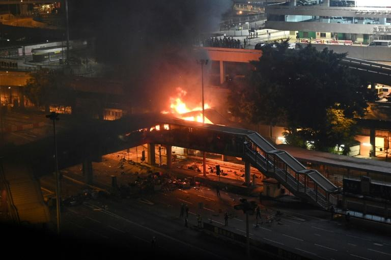 Police tried to retake a footbridge over a tunnel in Hong Kong but were met by a barrage of petrol bombs that caused a huge fire (AFP Photo/Philip FONG)