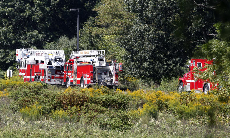 Firetrucks are lined-up not far from the site of a helicopter crash Saturday, Sept. 15, 2012, in West Windsor, N.J. West Windsor police Lt. Robert Garofolo said that witnesses reported to police that the helicopter struck a flock of birds shortly before crashing in a corn field. (AP Photo/Mel Evans)